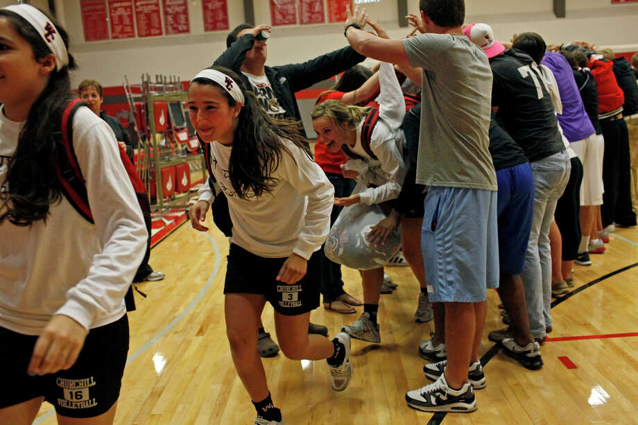 The Churchill Volleyball team runs through a tunnel made by students to celebrate their win against New Braunfels Canyon in a Class 5A first round playoff match at Judson High School on Tuesday, Oct. 30, 2012. Photo: Lisa Krantz, San Antonio Express-News / San Antonio Express-News