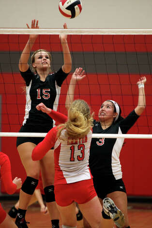 Churchill's Shelby Arnold (15), left, and Tori Guerra, right, go up against New Braunfels Canyon's Katie Cavanaugh during their Class 5A first round playoff match at Judson High School on Tuesday, Oct. 30, 2012. Photo: Lisa Krantz, San Antonio Express-News / San Antonio Express-News