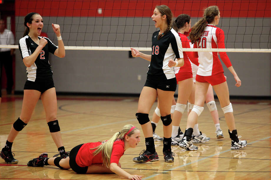 Churchill's Karley York, left, and Taylor Martinez, right, celebrate a point as Amy Nettles gets up during their Class 5A first round playoff match against New Braunfels Canyon at Judson High School on Tuesday, Oct. 30, 2012. Photo: Lisa Krantz, San Antonio Express-News / San Antonio Express-News