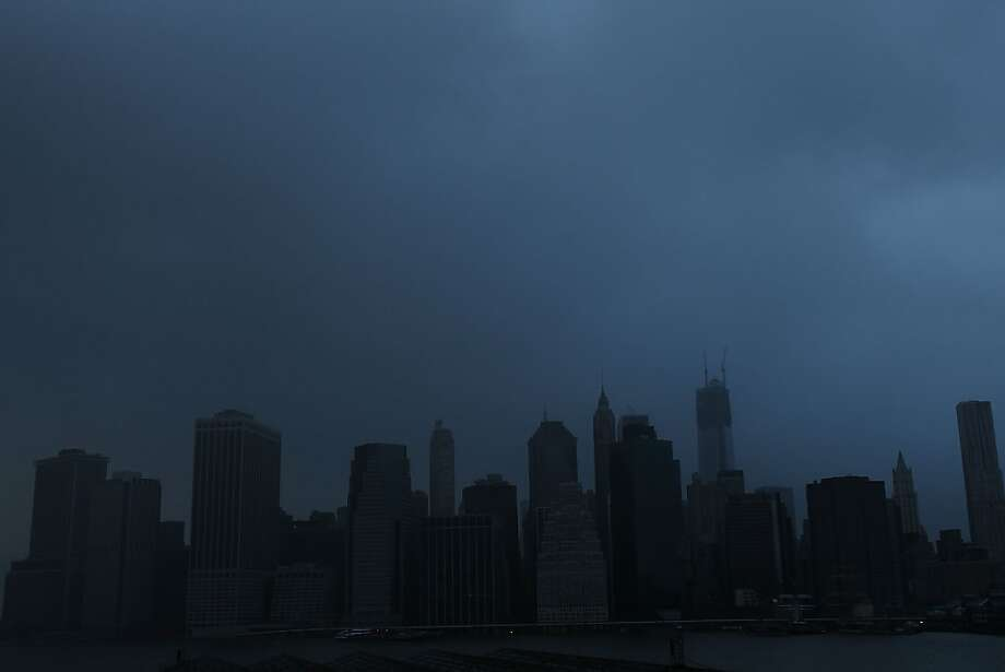 A darkened Manhattan is viewed after much of the city lost electricity due to the affects of Hurricane Sandy on October 30, 2012 in New York, United States. At least 33 people were reported killed in the United States by Sandy as millions of people in the eastern United States have awoken to widespread power outages, flooded homes and downed trees. New York City was his especially hard with wide spread power outages and significant flooding in parts of the city. (Photo by Spencer Platt/Getty Images) Photo: Spencer Platt, Getty Images