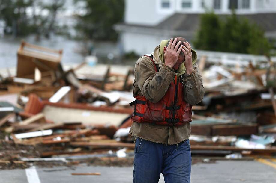 Brian Hajeski, 41, of Brick, N.J., reacts after looking at debris of a home that washed up on to the Mantoloking Bridge the morning after superstorm Sandy rolled through, Tuesday, Oct. 30, 2012, in Mantoloking, N.J. Sandy, the storm that made landfall Monday, caused multiple fatalities, halted mass transit and cut power to more than 6 million homes and businesses. (AP Photo/Julio Cortez) Photo: Julio Cortez, Associated Press