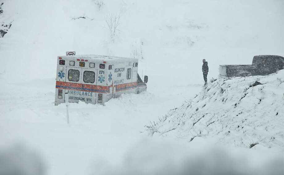 An ambulance is stuck in over a foot of snow off of Highway 33 West, near Belington, W.Va. on Tuesday, Oct. 30, 2012, in Belington, W.Va. Superstorm Sandy buried parts of West Virginia under more than a foot of snow on Tuesday, cutting power to at least 264,000 customers and closing dozens of roads. At least one death was reported. The storm not only hit higher elevations hard as predicted, communities in lower elevations got much more than the dusting of snow forecasters had first thought from a dangerous system that also brought significant rainfall, high wind gusts and small-stream flooding. (AP Photo/Robert Ray) Photo: Robert Ray, Associated Press