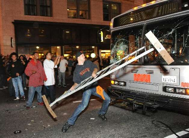 This photo of a man smashing the front window of a Muni bus was widely circulated online. (Photo by Susana Bates, Special to the Chronicle)