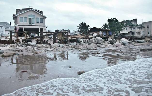 A beachfront house is damaged in the aftermath of yesterday's surge from superstorm Sandy, Tuesday, Oct. 30, 2012, in Coney Island's Sea Gate community in New York. (AP Photo/Bebeto Matthews) Photo: Bebeto Matthews