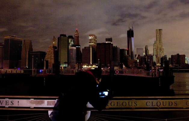 A woman photographs the Manhattan skyline, Tuesday, Oct. 30, 2012 in New York. Much of lower Manhattan is without electric power following the impact of superstorm Sandy. (AP Photo/Mark Lennihan) Photo: Mark Lennihan
