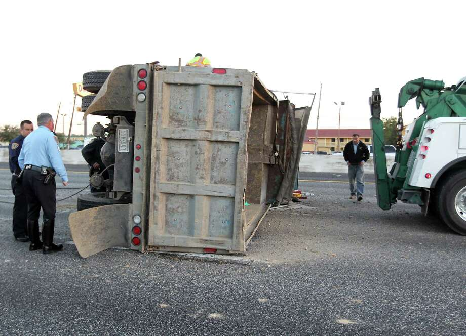 Houston Police officer investigate a one vehicle accident involving an overturned dump truck on I 10 East just past the John Ralston road exit Wednesday, Oct. 31, 2012, in Houston. The driver of the accident which occurred at 5:35 am had all east bound lanes of I 10 closed will be ticketed for failure to drive in a single lane according to HPD Sgt. W.J. Wehr. Photo: James Nielsen, . / © Houston Chronicle 2012
