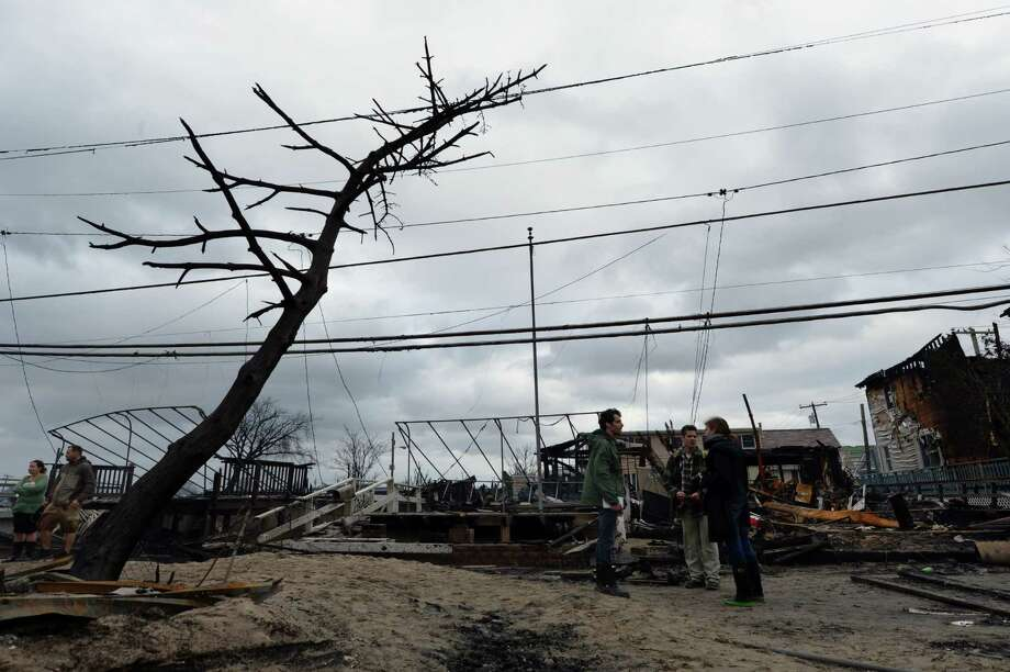 TOPSHOTS People view damage in a neighborhood in the Breezy Point area of Queens in New York on October 30, 2012 after fire destroyed about 80 homes as a result of Hurricane Sandy which hit the area October 29. The death toll from superstorm Sandy has risen to 35 in the United States and Canada, and was expected to climb further as several people remained missing, officials said. Officials in the states of Connecticut, Maryland, New York, New Jersey, North Carolina, Pennsylvania, Virginia and West Virginia all reported deaths from the massive storm system, while Toronto police said a Canadian woman was killed by flying debris.    AFP PHOTO/Stan HONDASTAN HONDA/AFP/Getty Images Photo: STAN HONDA, AFP/Getty Images / AFP