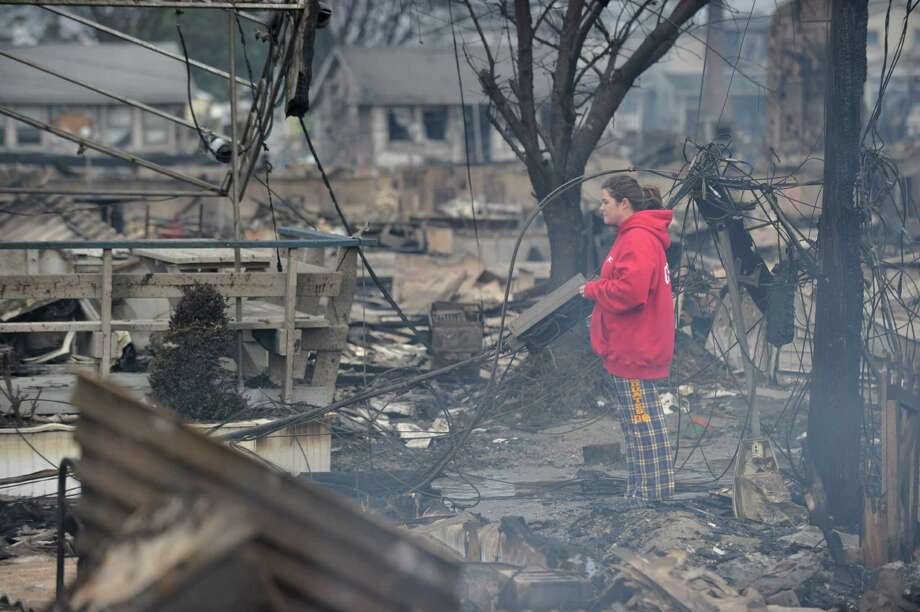 TOPSHOTS  A woman views still smoldering damage in a neighborhood in the Breezy Point area of Queens in New York on October 30, 2012 after fire destroyed about 80 homes as a result of Hurricane Sandy which hit the area October 29. The death toll from superstorm Sandy has risen to 35 in the United States and Canada, and was expected to climb further as several people remained missing, officials said. Officials in the states of Connecticut, Maryland, New York, New Jersey, North Carolina, Pennsylvania, Virginia and West Virginia all reported deaths from the massive storm system, while Toronto police said a Canadian woman was killed by flying debris.    AFP PHOTO/Stan HONDASTAN HONDA/AFP/Getty Images Photo: STAN HONDA, AFP/Getty Images / AFP
