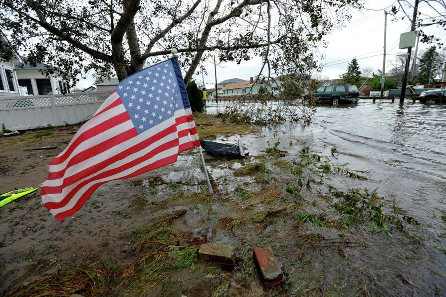 An American flag flies from the front yard of a house in a flood damaged area October 30, 2012 in th