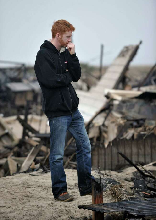 Gavin Byrne views damage in the Breezy Point area of Queens in New York on October 30, 2012 after fire destroyed about 80 homes as a result of Hurricane Sandy which hit the area on October 29. The death toll from superstorm Sandy has risen to 35 in the United States and Canada, and was expected to climb further as several people remained missing, officials said. Officials in the states of Connecticut, Maryland, New York, New Jersey, North Carolina, Pennsylvania, Virginia and West Virginia all reported deaths from the massive storm system, while Toronto police said a Canadian woman was killed by flying debris.    AFP PHOTO/Stan HONDASTAN HONDA/AFP/Getty Images Photo: STAN HONDA, AFP/Getty Images / AFP