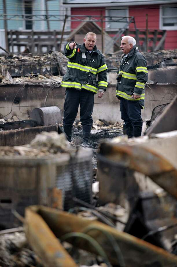 Two New York City Fire Department firefighters view damage in a neighborhood in the Breezy Point area of Queens in New York on October 30, 2012 after fire destroyed about 80 homes as a result of Hurricane Sandy which hit the area October 29. The death toll from superstorm Sandy has risen to 35 in the United States and Canada, and was expected to climb further as several people remained missing, officials said. Officials in the states of Connecticut, Maryland, New York, New Jersey, North Carolina, Pennsylvania, Virginia and West Virginia all reported deaths from the massive storm system, while Toronto police said a Canadian woman was killed by flying debris.   AFP PHOTO/Stan HONDASTAN HONDA/AFP/Getty Images Photo: STAN HONDA, AFP/Getty Images / AFP