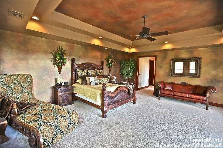 The master bedroom has plush carpeting, recessed lighting and a raised ceiling.