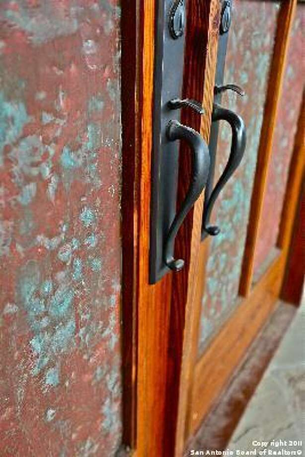 These doors have wrought-iron handles and a painted design.