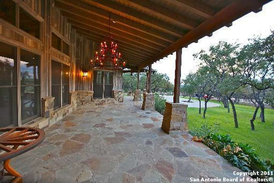 The covered deck includes a handing chandelier and looks out on the expansive acreage.