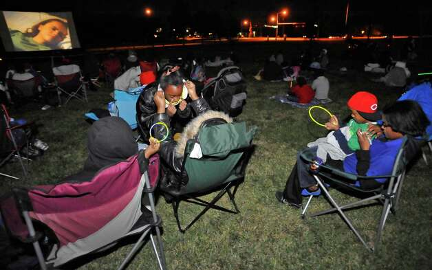 The Theodore Johns Library on Fannett Road in Beaumont hosted a free showing of Casper, the movie, Monday evening complete with popcorn and candy. Wrapped in a blanket against the cold, and sitting on a warm lap, Aaron Bugas, right, 5, plays with a glow stick as his mom, Kristen checks her phone.  Beaumont Parks and Recreation Department employees, handled the logistics of putting on the show. Over 100 people braved the cold temperatures, wrapped in blankets, to see it.  Dave Ryan/The Enterprise Photo: Dave Ryan