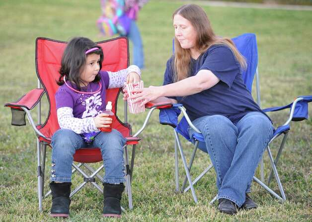 Katherine Mireles, right, shares a popcorn with her granddaughter Trinity Rivera, 7, before the show started. The Theodore Johns Library on Fannett Road in Beaumont hosted a free showing of Casper, the movie, Monday evening complete with popcorn and candy. Beaumont Parks and Recreation Department employees handled the logistics of putting on the show. Over 100 people braved the cold temperatures, wrapped in blankets, to see it.  Dave Ryan/The Enterprise