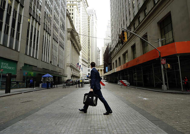 A man looks up towards the New York Stock Exchange as  he returns to work on Wall Street on October 31, 2012 as New Yorkers cope with the aftermath  of Hurricane Sandy.  The storm left large parts of ew York City without power and transportation.  The John F. Kennedy and Newark Liberty airports, both of which serve New York City, are reopening Wednesday morning after being closed for days by Hurricane Sandy, the local port authority said.  Photo: TIMOTHY A. CLARY, AFP/Getty Images / 2012 AFP