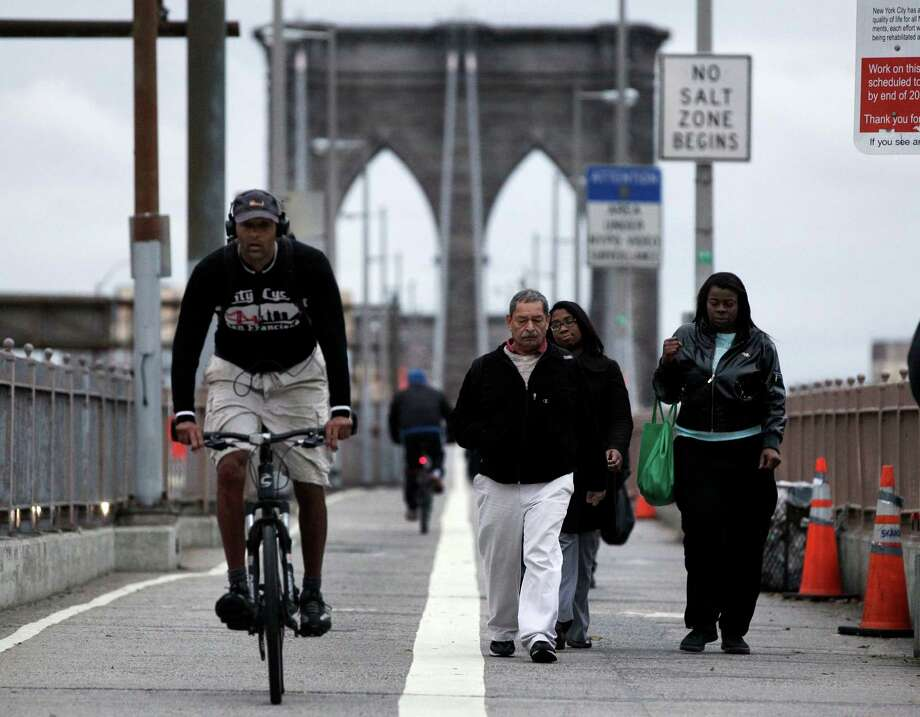 Morning commuters walk and bicycle across New York's Brooklyn Bridge, Wednesday, Oct. 31, 2012. On the Brooklyn Bridge, closed earlier because of high winds, joggers and bikers made their way across the span before sunrise. Car traffic on the bridge was busy, and slowed as it neared Manhattan. Photo: Richard Drew