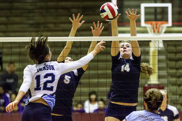 Smithson Valley's Allison Grona (14) and Carly Moczygemba go up to block a shot by Johnson's Shelby Walker during the second set of their bidistrict match with Johnson at the Alamo Convocation Center on Oct. 30, 2012.  Smithson Valley swept defending Region IV-5A champion Johnson 25-12, 25-17, 25-22 to advance to the second round where they will face Taft on Nov. 2 at Boerne Champion.  Marvin Pfeiffer / Prime Time Newspapers Photo: MARVIN PFEIFFER, Marvin Pfeiffer / Prime Time New / mpfeiffer@primetimenewspapers.co