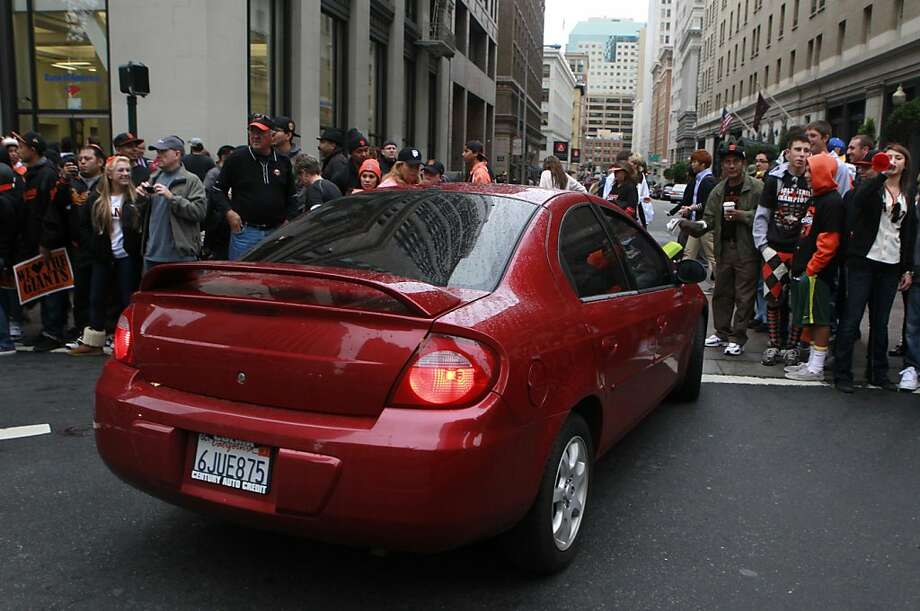 A commuter thries to squeeze through a surging crowd blocking Montomgery Street before the Giants' World Series victory parade on Market Street in San Francisco, Calif. on Wednesday, Oct. 31, 2012. Photo: Paul Chinn, The Chronicle