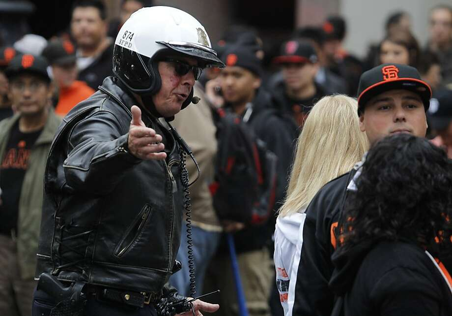 A police officer tells fans to move off of Montgomery Street before the street closures go into effect for the Giants' World Series victory parade on Market Street in San Francisco, Calif. on Wednesday, Oct. 31, 2012. Photo: Paul Chinn, The Chronicle