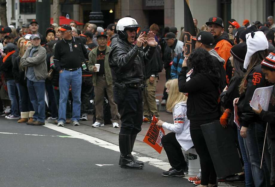 A police officer orders fans to move off of Montgomery Street before the street closures go into effect for the Giants' World Series victory parade on Market Street in San Francisco, Calif. on Wednesday, Oct. 31, 2012. Photo: Paul Chinn, The Chronicle