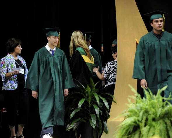 Matthew Patino, second from left, and his brother, Mark, right, graduate from Holmes High School on Friday night, June 1, 2012. Photo: Billy Calzada, San Antonio Express-News / San Antonio Express-News