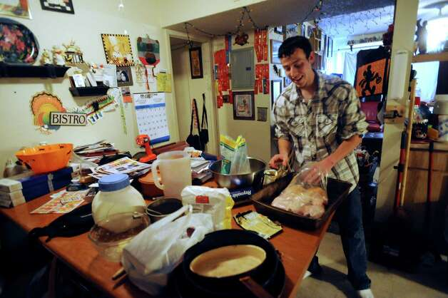 Matthew Patino prepares a chicken dinner for his family on Wednesday, Oct. 24, 2012. Patino is an avid runner despite losing a lower leg to cancer. Photo: Billy Calzada, San Antonio Express-News / San Antonio Express-News