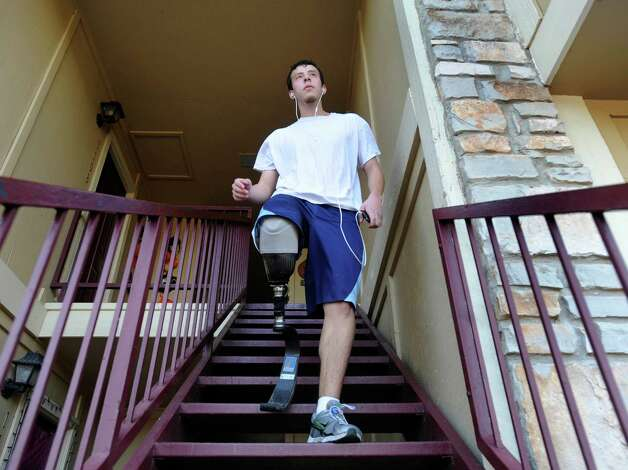 Matthew Patino leaves his family's apartment for a run on Wednesday, Oct. 24, 2012. He has two prosthetic legs, one for running and one for everyday use. Photo: Billy Calzada, San Antonio Express-News / San Antonio Express-News