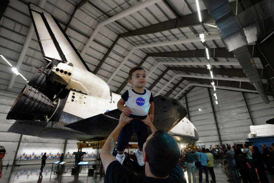 Andrew Hanna, who works for NASA, holds up 17-month-old son Aaron during the space shuttle Endeavour exhibit grand opening ceremony at the new Samuel Oschin Pavilion of the California Science Center on Tuesday in Los Angeles. Photo: Kevork Djansezian, Getty Images / 2012 Getty Images