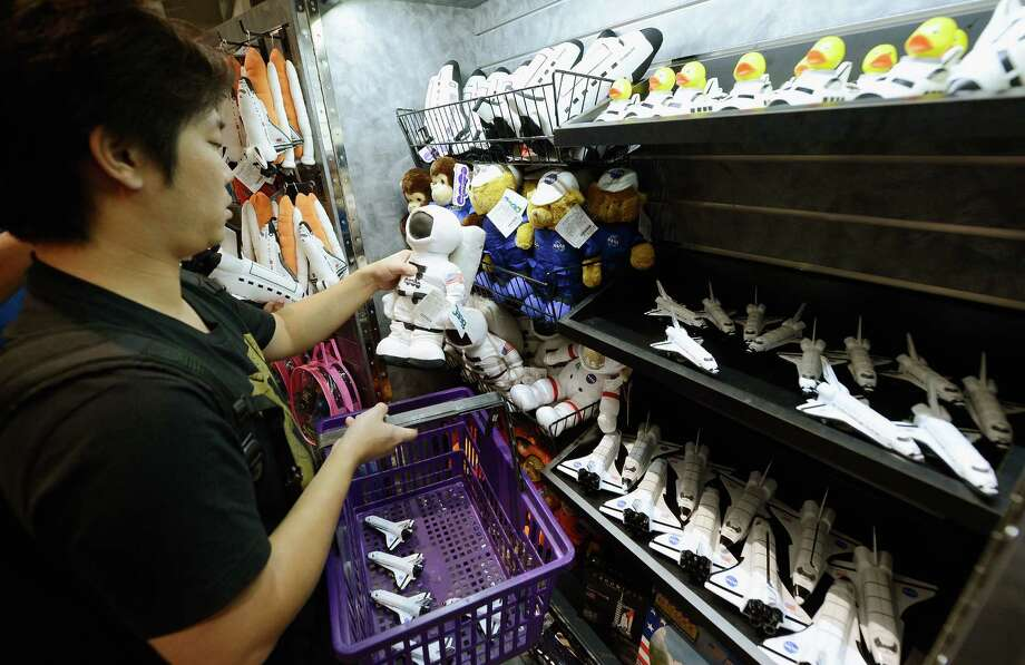 A visitor looks at souvenirs after the grand opening ceremony of the space shuttle Endeavour exhibit at the new Samuel Oschin Pavilion of the California Science Center on Tuesday in Los Angeles. Photo: Kevork Djansezian, Getty Images / 2012 Getty Images