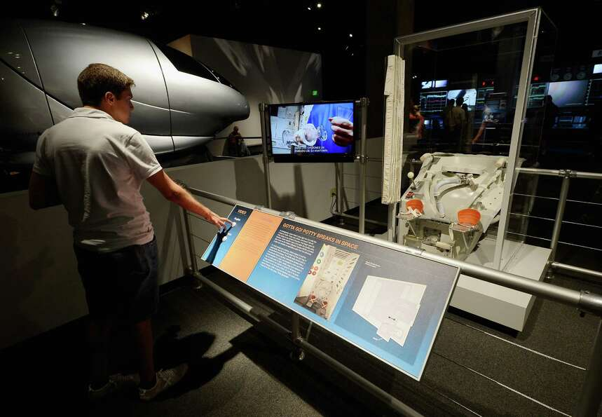 A visitor looks at an exhibit showing the bathroom on the space shuttle Endeavour after the grand op