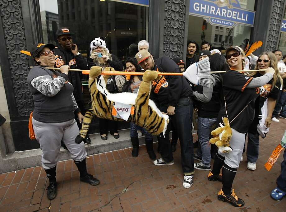 DeDe Krake, left, and Stacy Hunt, right, of Auburn, Calif., carry a tiger on a broom while walking along Market Street before the start of the San Francisco Giants World Series victory parade Wednesday, Oct. 31, 2012 in San Francisco.  The team's second championship in three years goes along Market Street and ends with a celebration in front of City Hall. (AP Photo/Eric Risberg) Photo: Eric Risberg, Associated Press