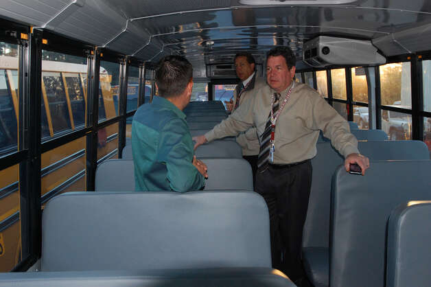 Jasper Superintendent Dr. Richard Skuza and Chris Coleman talk with a representative from Thomas Buses after the delivery of seven new school buses to Jasper ISD. Photo: Jimmy Galvan