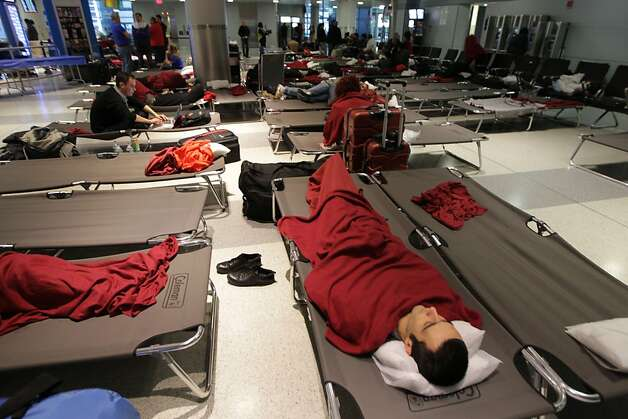 Passengers at New York's John F. Kennedy International Airport remain stranded on October 31, 2012 even as the airport resumes some service after being closed due to Hurricane Sandy. Kennedy and Newark Liberty airports, both of which serve New York City, reopened Wednesday morning after being closed for days by Hurricane Sandy, the local port authority said. Two New York airports and Wall Street reopened, but the crippled subway system, traffic-clogged roads and large areas still without power pose a daunting hurdle before the Big Apple can declare itself back to normal. Photo: Mehdi Taamallah, AFP/Getty Images