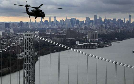 A New York Air National Guard helicopter flies above the George Washington Bridge towards Manhattan, Wednesday, Oct. 31, 2012 in New York. Gov. Andrew Cuomo, Sen. Kirsten Gillibrand, D-NY, Sen. Charles Schumer, D-NY, and local officials took the flight over the city, Nassau and Westchester counties to get an assessment of damages from superstorm Sandy. Photo: Mark Lennihan, Associated Press
