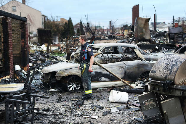 A firefighter stands among the remains of homes burned down in the Rockaway neighborhood during Hurricane Sandy on October 31, 2012 in the Queens borough of New York City. With the death toll currently at 55 and millions of homes and businesses without power, the US east coast is attempting to recover from the affects of floods, fires and power outages brought on by Hurricane Sandy. JFK airport in New York and Newark airport in New Jersey expect to resume flights on Wednesday morning and the New York Stock Exchange commenced trading after being closed for two days. Photo: Spencer Platt, Getty Images / 2012 Getty Images
