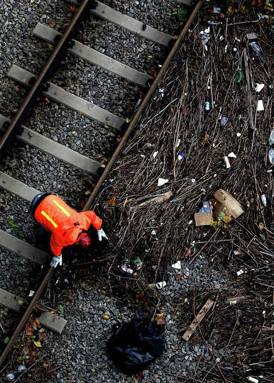 An NJ Transit worker clears debris from tracks as clean up operations proceed on October 31, 2012 in