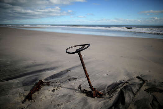 Old buried car parts on the beach are unearthed by Hurricane Sandy, on October 31, 2012 in Long Beach Island, New Jersey. Earlier in the week Hurricane Sandy made landfall on New Jersey coastline bringing damaging winds and record floodwaters. Photo: Mark Wilson, Getty Images / 2012 Getty Images