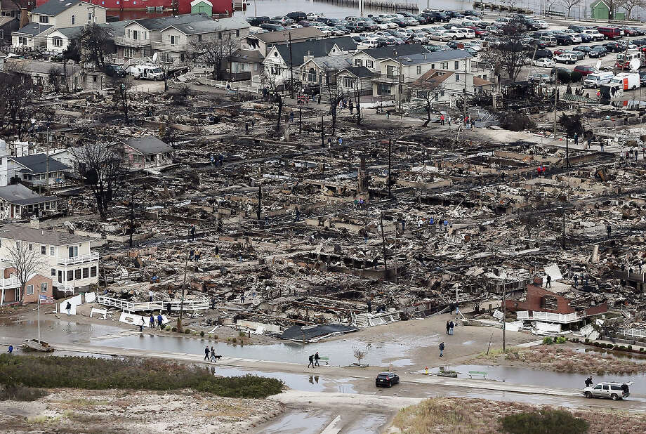 People walk near the remains of burned homes after Hurricane Sandy on October 31, 2012 in the Breezy Point neighborhood of the Queens borough of New York City. Over 50 homes were reportedly destroyed in a fire during the storm. At least 50 people were reportedly killed in the U.S. by Sandy. New York City was hit especially hard with wide spread power outages and significant flooding in parts of the city. Photo: Mario Tama, Getty Images / 2012 Getty Images