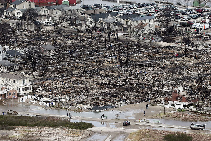 People walk near the remains of burned homes after Hurricane Sandy on October 31, 2012 in the Breezy