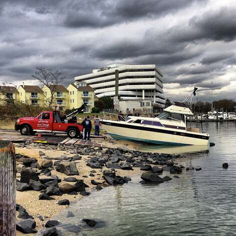 A tow truck pulls a boat that had been found sunk in the Stamford Harbor following Hurricane Sandy back to dry land. Photo: Kara Glover Billhardt