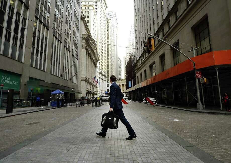 A man looks up towards the New York Stock Exchange as  he returns to work on Wall Street on October 31, 2012 as New Yorkers cope with the aftermath  of Hurricane Sandy.  The storm left large parts of ew York City without power and transportation.  The John F. Kennedy and Newark Liberty airports, both of which serve New York City, are reopening Wednesday morning after being closed for days by Hurricane Sandy, the local port authority said. Photo: TIMOTHY A. CLARY, AFP/Getty Images / AFP
