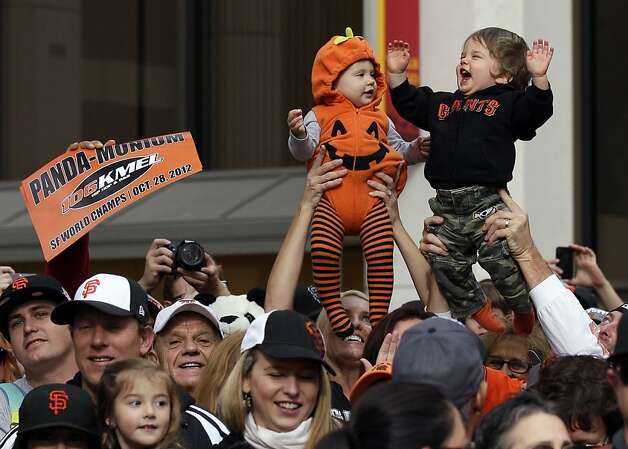 Fans hold up their children, cousins Reagan Hagerstrand, 10-months, and Ryan Magnani, 1, right, during the San Francisco Giants World Series victory parade, Wednesday, Oct. 31, 2012, in San Francisco. (AP Photo/Jeff Chiu) Photo: Jeff Chiu, Associated Press