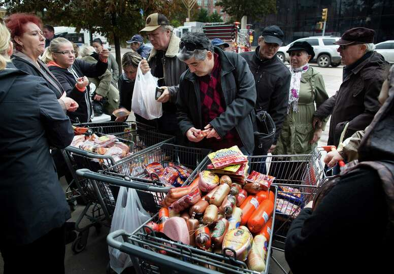 A customer browses food piled into shopping carts on Brighton Beach Avenue, Wednesday, Oct. 31, 2012