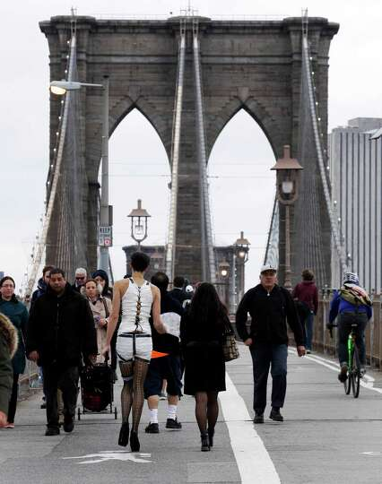 Commuters, including one man dressed for Halloween, cross New York's Brooklyn Bridge, Wednesday, Oct