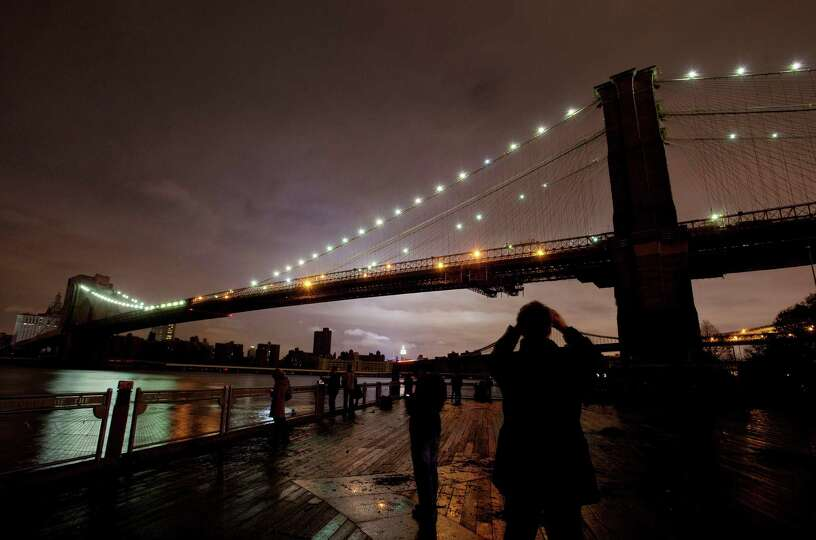 People photograph the Brooklyn Bridge and the Manhattan skyline, Tuesday, Oct. 30, 2012 in New York.