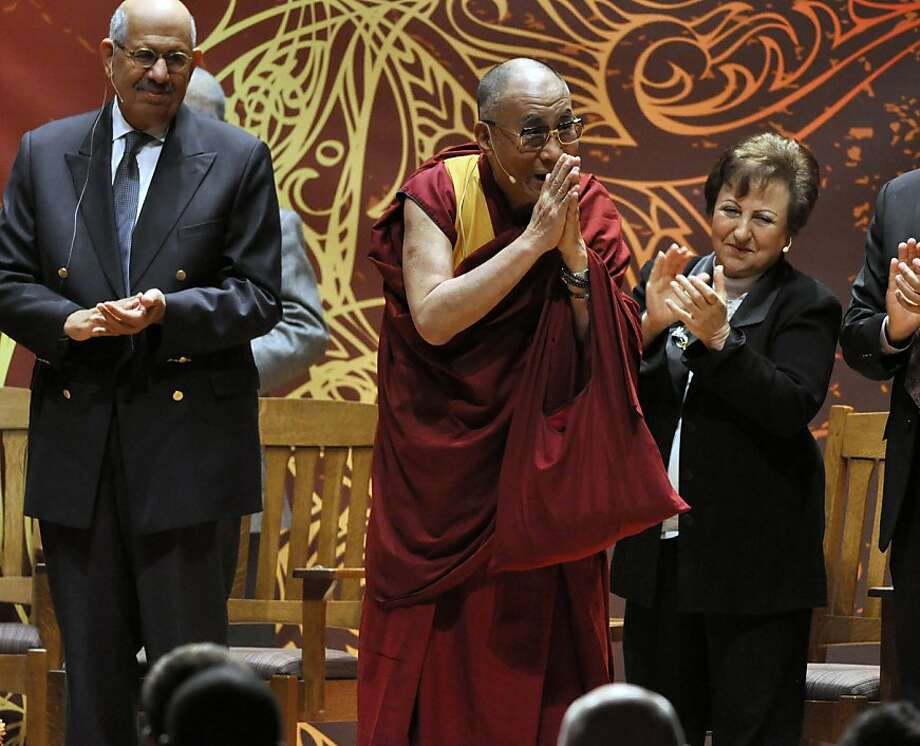 His Holiness the 14th Dalai Lama acknowledges the audience after being introduced, during the symposium on The Rise of Democracy in the Middle East as part of the Common Ground forPeace two-day forum in Syracuse, N.Y., Monday, Oct. 8, 2012. He is flanked by Mohamed ElBaradei, left, and Shirin Ebadi, right. (AP Photo/Kevin Rivoli) Photo: Kevin Rivoli, Associated Press