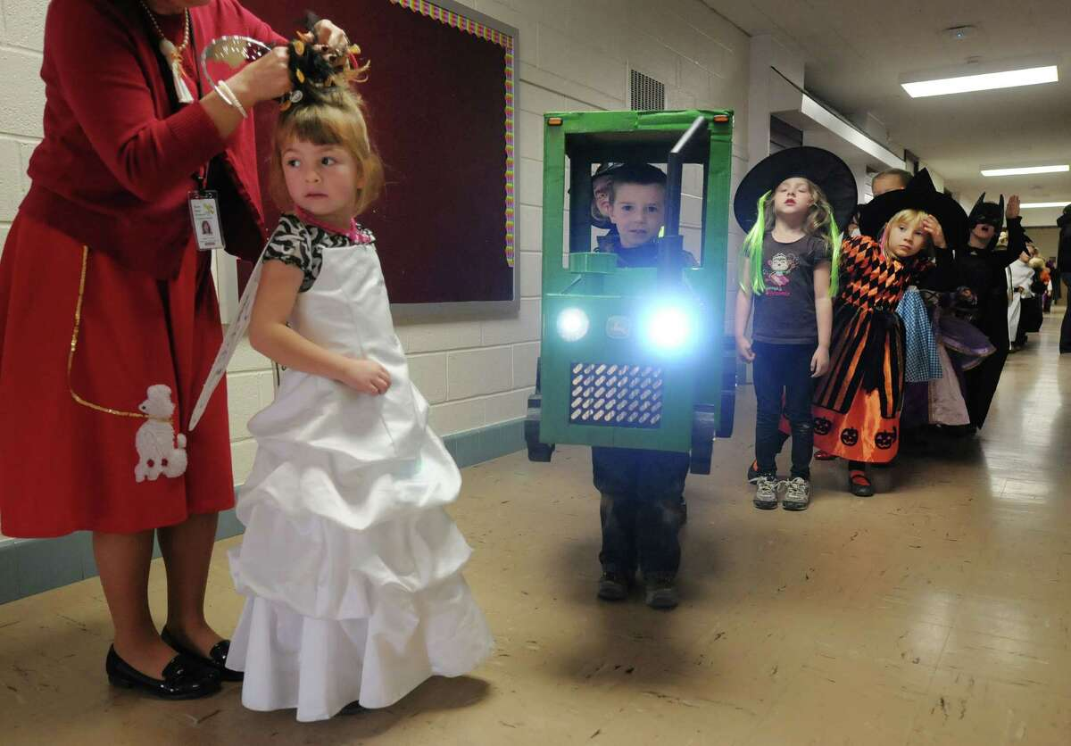 Kindergartners Kara Joslyn, left, gets her hair fixed as her cousin Garret Hempstead, dressed as a tractor, and the rest of their class get ready for the start of the Halloween parade at the Berne-Knox-Westerlo Elementary School on Wednesday, Oct. 31, 2012, in Berne, NY. The long-held tradition at the school involves the children in grades kindergarten through five dressing up and parading outside past family members before heading into the secondary-level school building and then heading back to their classes in the elementary school. (Paul Buckowski / Times Union)