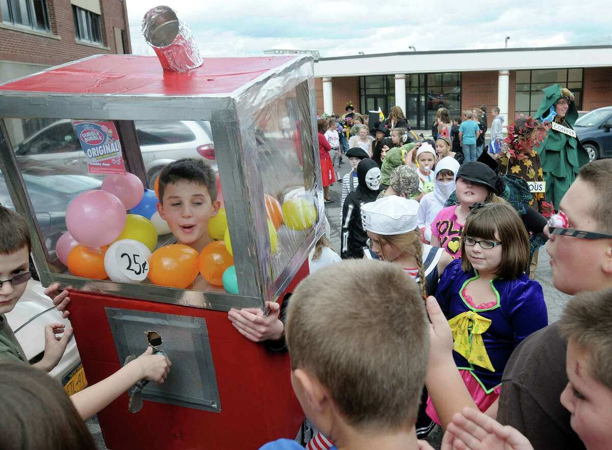 Students crowd around fellow student Cardell Iarusso, 10, who was handing out gum balls through his costume as a gum ball machine during the Halloween parade at the Berne-Knox-Westerlo Elementary School on Wednesday, Oct. 31, 2012, in Berne, NY. (Paul Buckowski / Times Union)